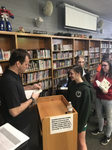 Author Brendan Reichs signs prize giveaway books for EverGreen Jr. High students